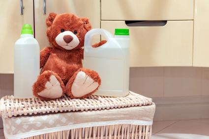A stuffed toy teddy bear is sitting on laundry basket in the bathroom next to detergent and rinse aid
