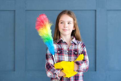 Cute girl in yellow rubber gloves and with rainbow duster