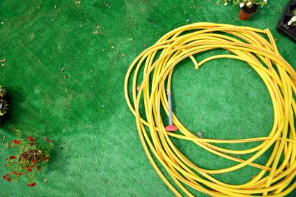 Watering hose on a green artificial grass