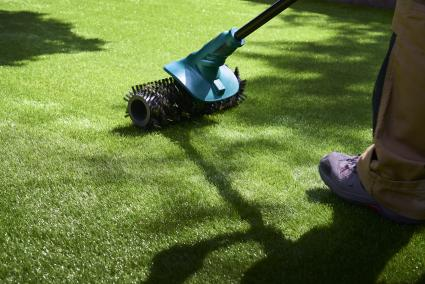 Worker uses electric brush to clean pile of fake grass