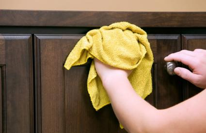 wiping kitchen wood cabinets