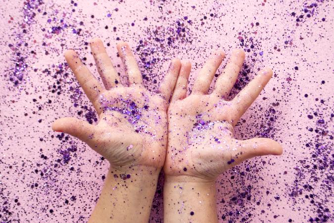Child's hands with purple color glitter