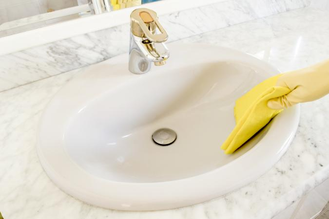 Cleaning porcelain sink with yellow gloves