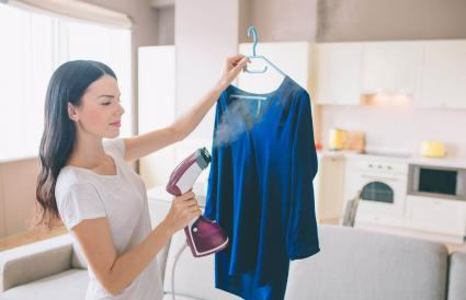 Woman is steaming blue shirt in room