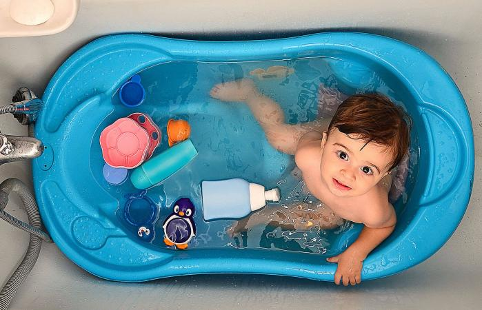 baby in tub with toys