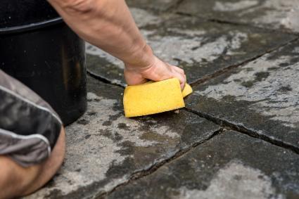 man scrubbing pavers