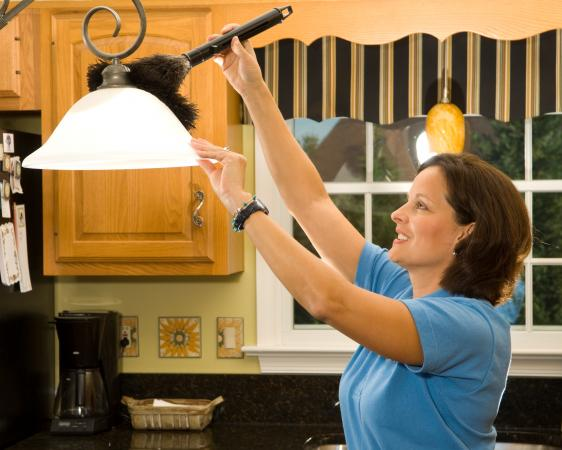 woman using duster to dust kitchen lamp ahdes