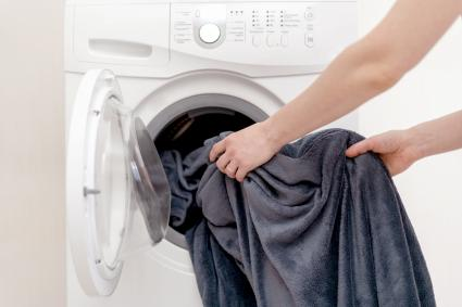 Woman hands put laundry into the white washing machine