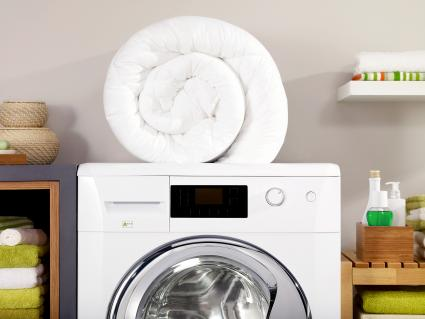 Folded down comforter on a washer in a laundry room