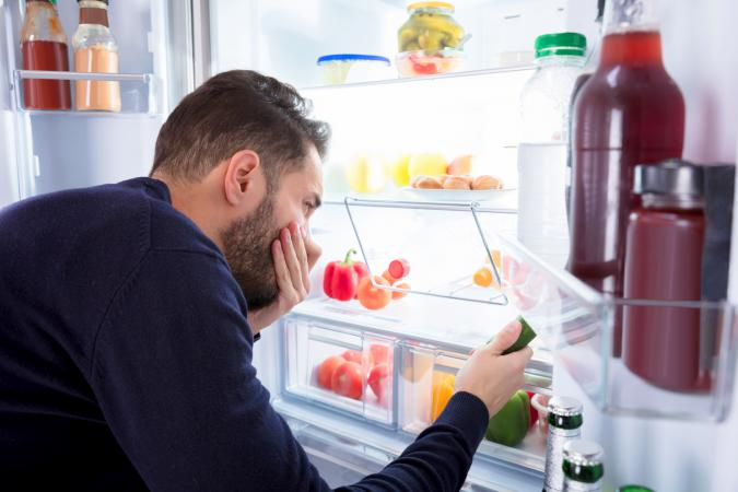 Man Noticing Smell Coming From Foul Food In Refrigerator
