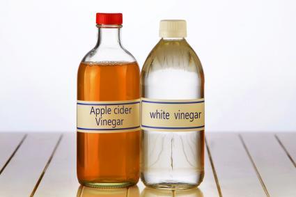 White vinegar and apple cider vinegar on table