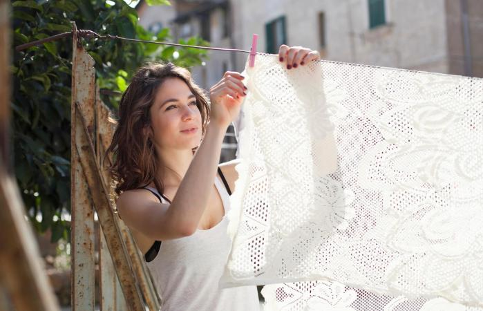 woman hanging table cloth on clothesline