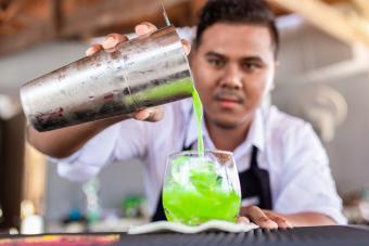 Bartender pouring Midori daiquiris