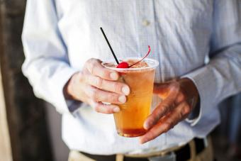 Man's hands holding an old fashioned cocktail