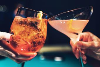 Hands of man and woman cheering with glasses of pink champagne