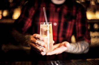 Bartender serving a Scotch Collins cocktail