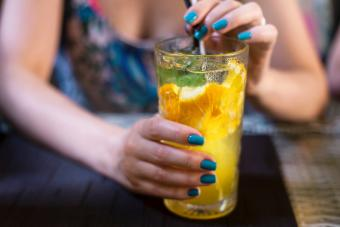 Woman holding glass of cold drink with orange juice