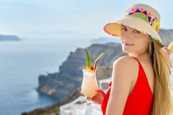 Woman holding pina colada cocktail and enjoying the view