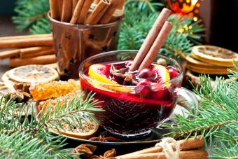 Christmas hot drink with citrus and cranberry in glass mug