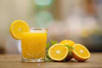 Brandy and fresh orange juice next to some orange slices on wooden table