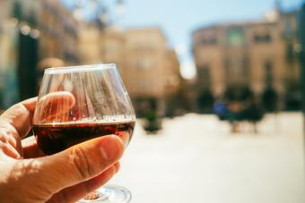 Hand holding a glass of cognac in terrace bar on a sunny day