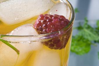 Glass of orange cocktail with raspberry