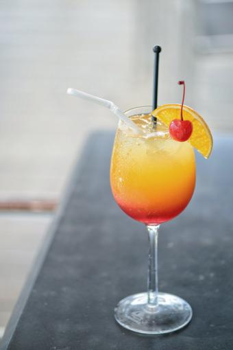 Red cocktail with an orange slice and cherry on the background of the a table