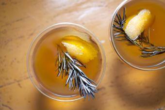 Artisan cocktails garnished with rosemary and orange zest