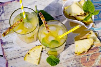 Two glasses with ice, cocos sirup and ananas juice, garnished with pieces of ananas and lemon balm