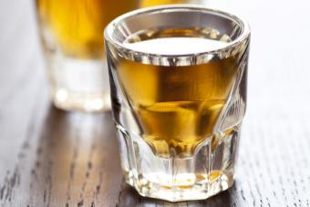 Three shot glasses full of whiskey on top of a bar table