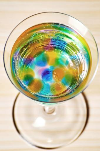 Glass with many colorful jelly balls and fizzy drink inside