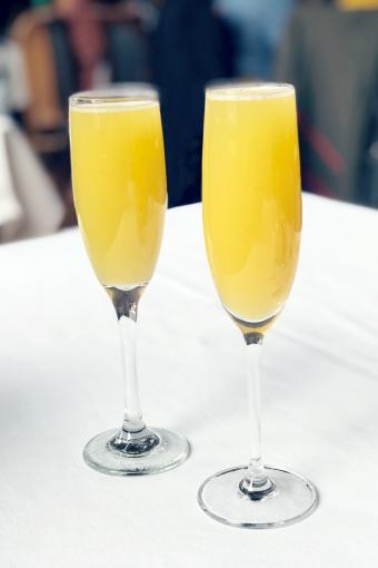 Two mango mimosas in champagne glasses