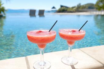 Two strawberry daiquiris beside a resort swimming pool