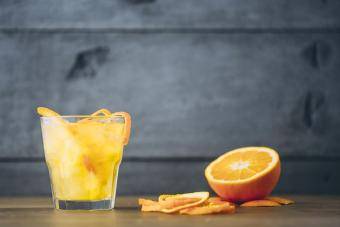 Vodka and orange juice with peel and sliced fruit