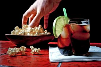Man's hand in popcorn bowl and charro negro in glass on bar counter
