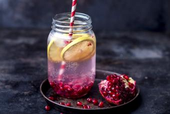 Fruit infused water with lemon slices, crushed pomegranate seeds and sparkling water