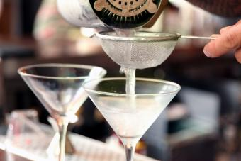 Bartender pouring martinis into chilled glasses