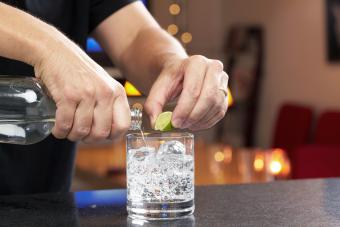 Hands squeezing lime and pouring gin or vodka into lowball glass with seltzer or tonic