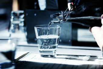 Gin Being Poured In Glass On Table