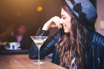 Young brunette woman sitting at a bar and enjoying a cocktail with a lemon twist