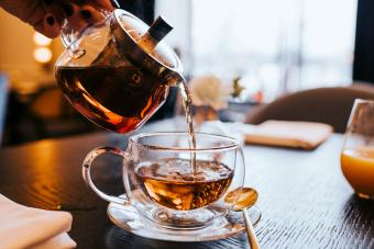 Hand pouring a cup of tea from a stylish transparent teapot