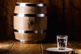 Old rustic oak barrel and glasses of high quality distilled alcohol
