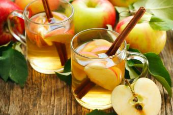 Two Apple Pie Toddy with apples on a wood table