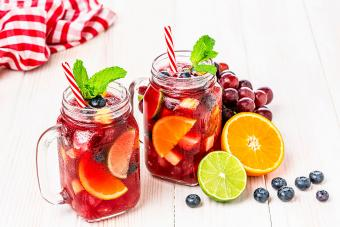Sangria with fruits on white table