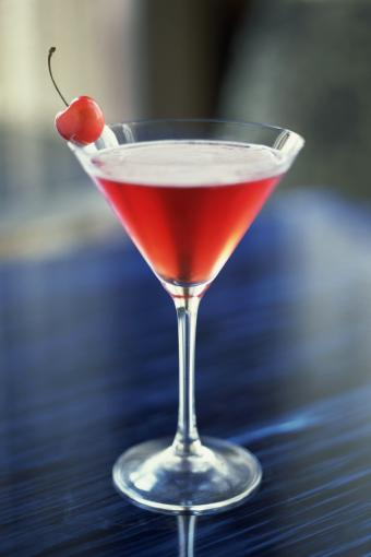 Martini cocktail with cherry on table in bar