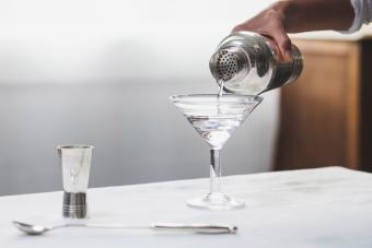 Cropped image of woman hand pouring alcohol in martini glass