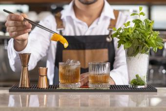 Bartender adding lemon peel in a drink