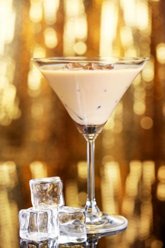 Baileys liqueur in glass on golden background