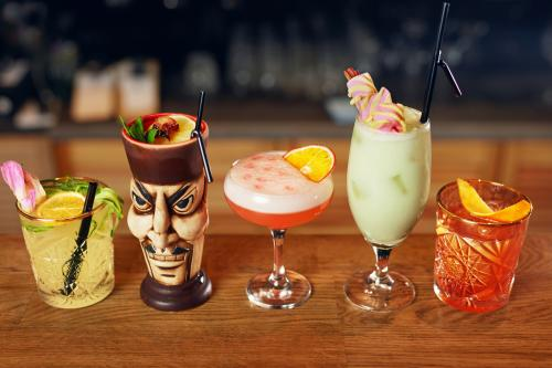 Tiki drinks lined up on a bar