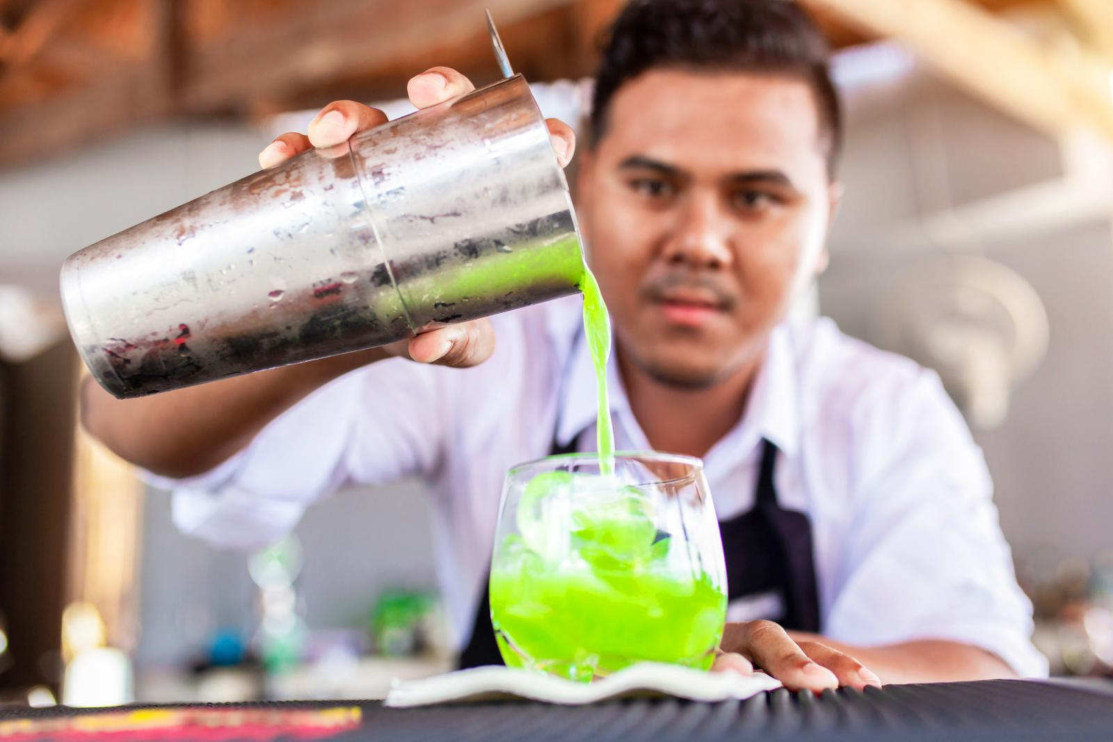 Male Bartender Preparing Green Cocktail In Bar